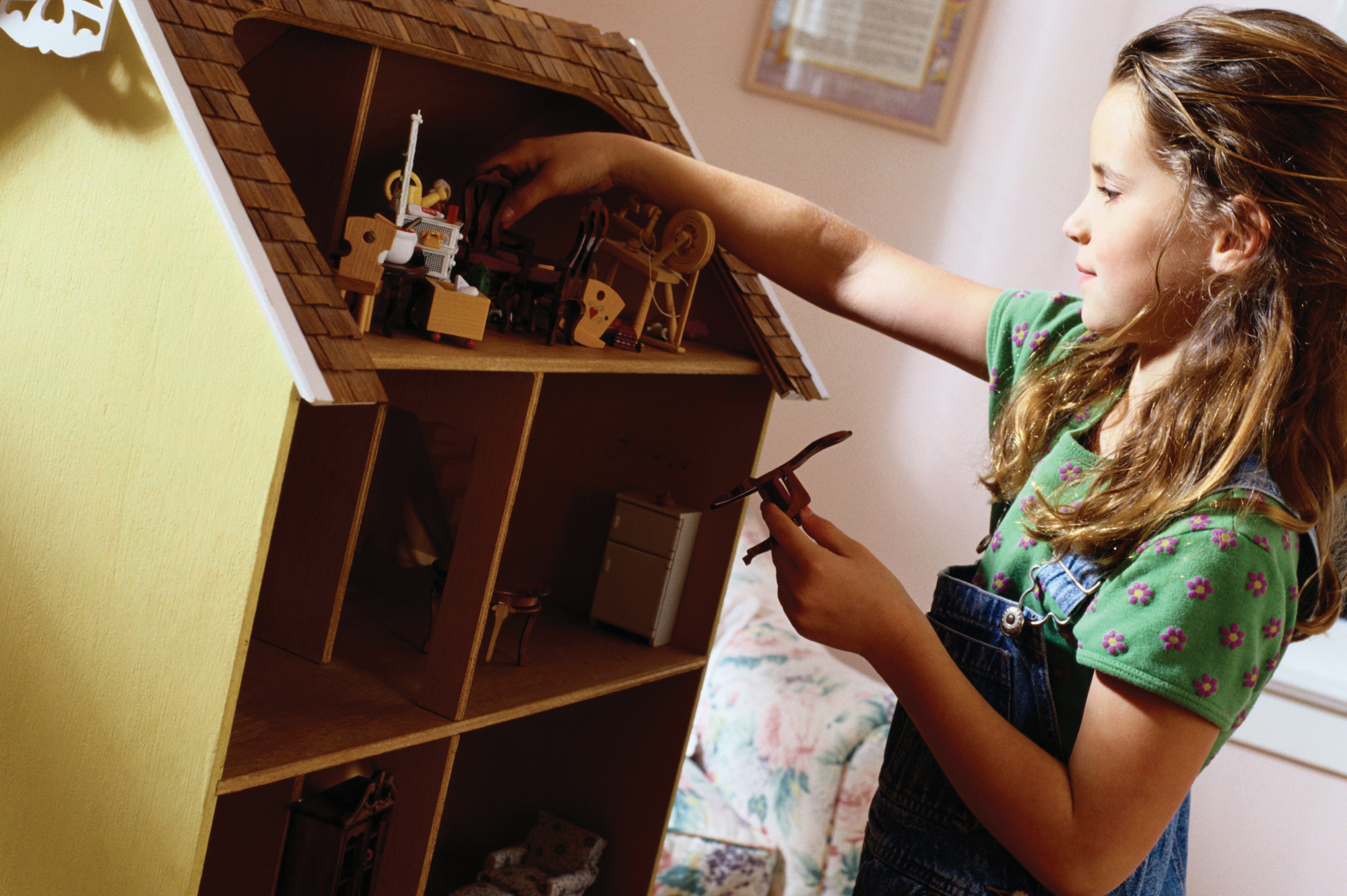 girl playing with dollhouse