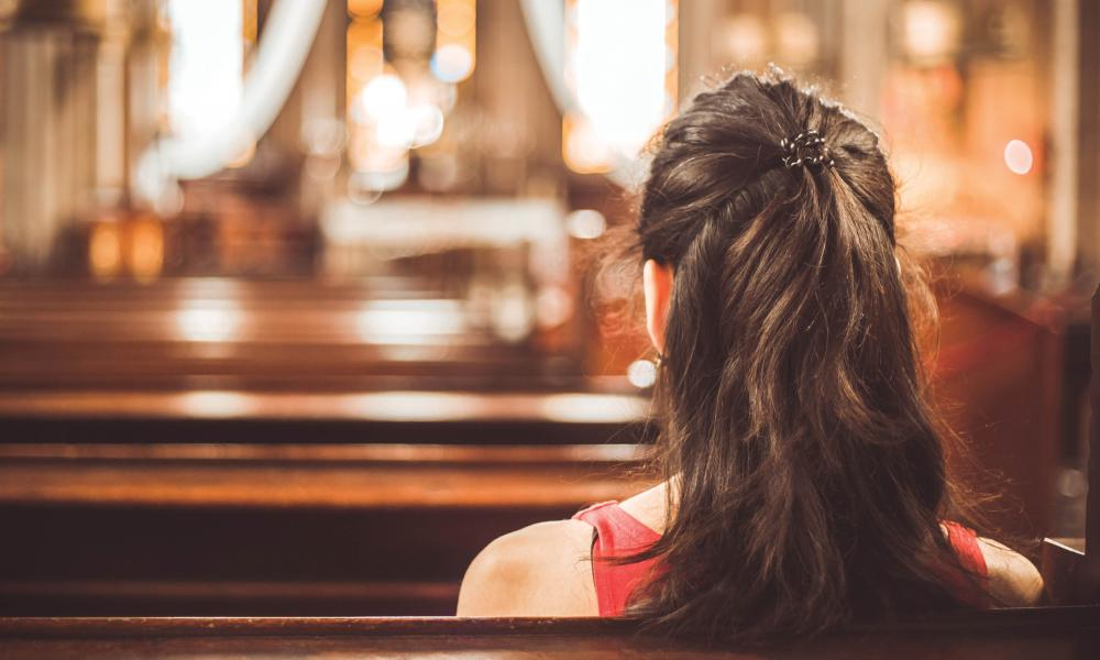 senior woman sitting in church pew.